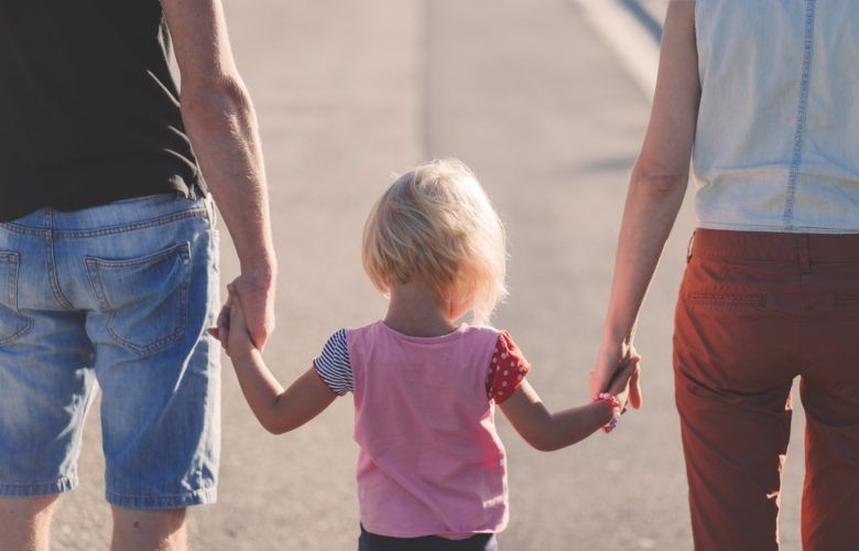 parents-holding-childs-hand-780x500